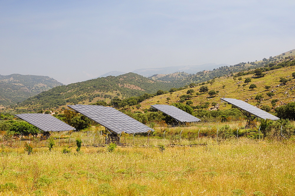 Solar farm with four Photovoltaic solar trackers, near Antissa, Lesbos (Lesvos), Greece. MORE INFO: Solar trackers automatically rotate and tilt photovoltaic panels to follow the sun throught the day, maximising sunlight absorpton rates. Several of these Solar farms have been built on Lesbos since 2010.
