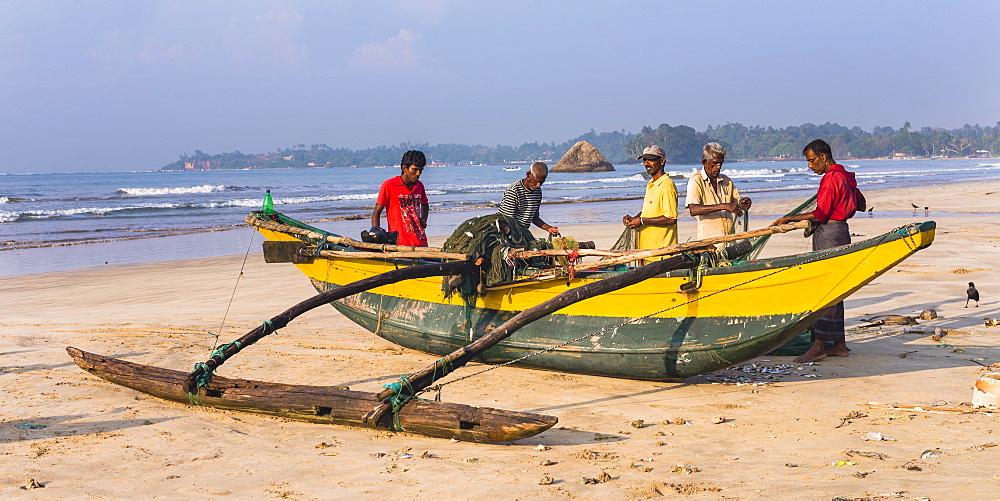 Fishermen sorting their catch on Weligama Beach, South Coast of Sri Lanka, Asia