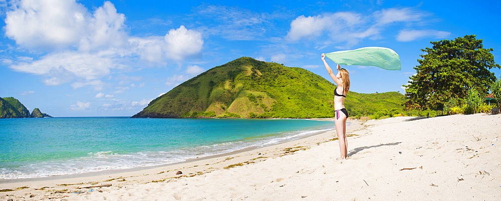 Woman celebrating freedom at Mawun Beach, a Tropical Paradise in South Lombok, Indonesia, Southeast Asia, Asia