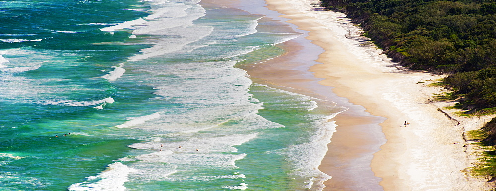Panoramic photo of surfers heading out to surf on Tallow Beach at Cape Byron Bay, New South Wales, Australia, Pacific