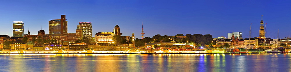 Panorama of Hamburg with view over the river Elbe to illuminated St. Pauli-Landungsbruecken with skyscrapers, Pegelturm, Heinric