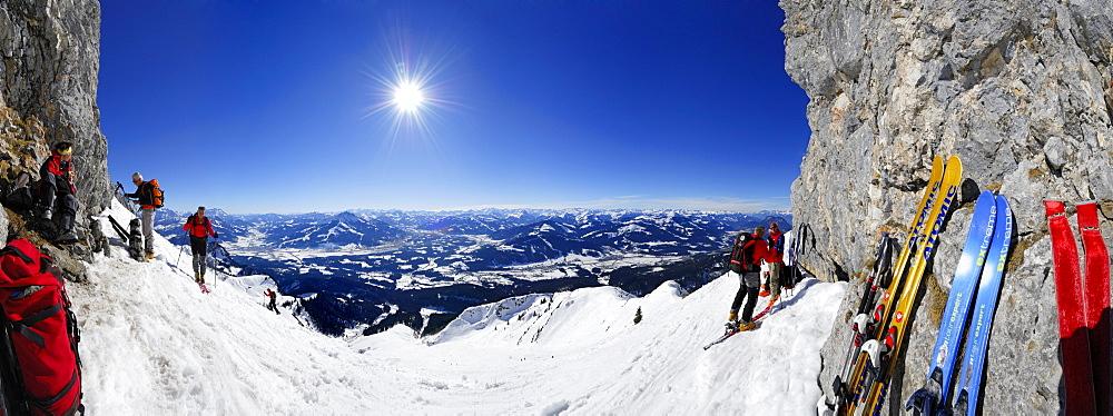 panorama with Kitzbuehel range, Hohe Tauern and Zillertal range and backcountry skiers ascending Herrenstein, Wilder Kaiser range, Kaisergebirge, Tyrol, Austria