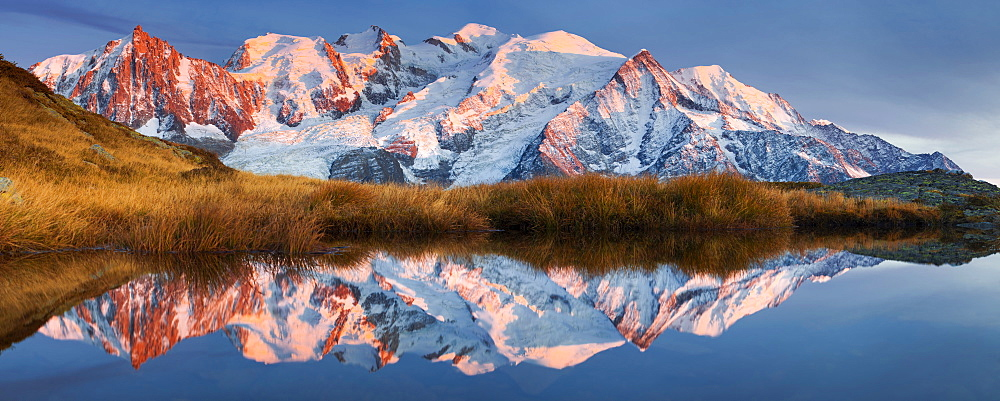 Alpen glow at the Mont Blanc Massif and its reflection in a mountain lake not far from the summit of Aiguillette du Brevent, Chamonix Valley, Haute-Savoie, France