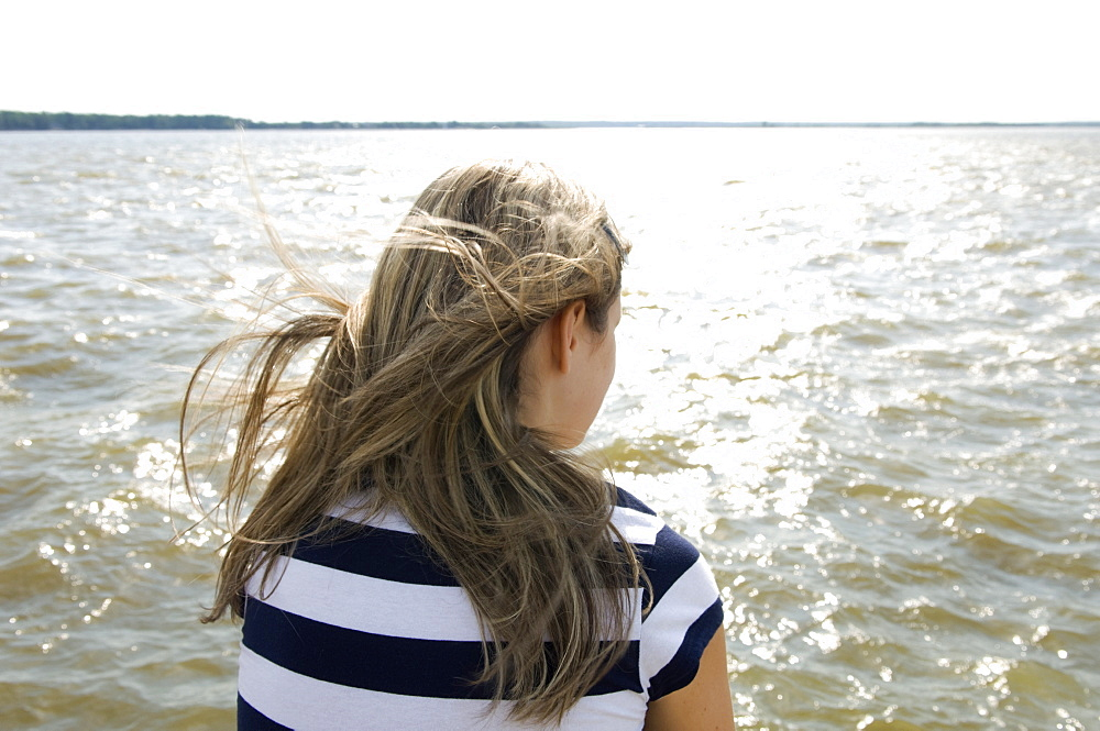 Teenager sitting by a lake, Victoria Beach, North of Winnipeg, Manitoba, Canada