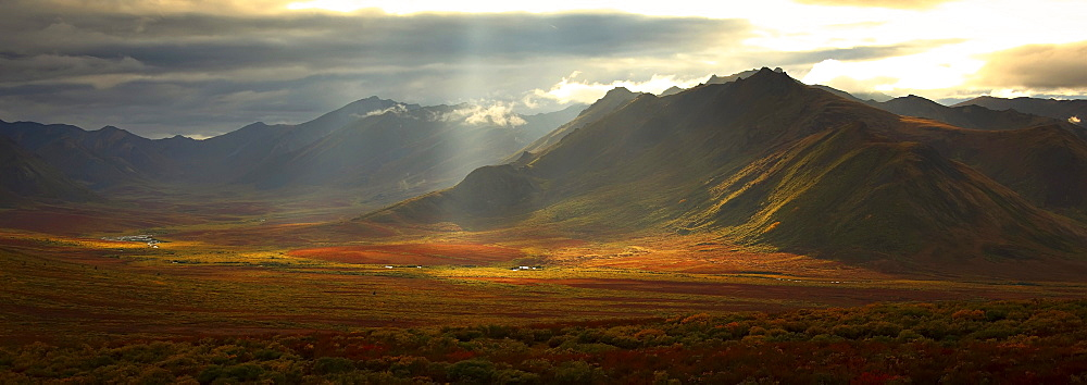 Panoramic image of the Cloudy Range with shafts of sunlight hitting the fall colours of the Dempster Highway, Yukon