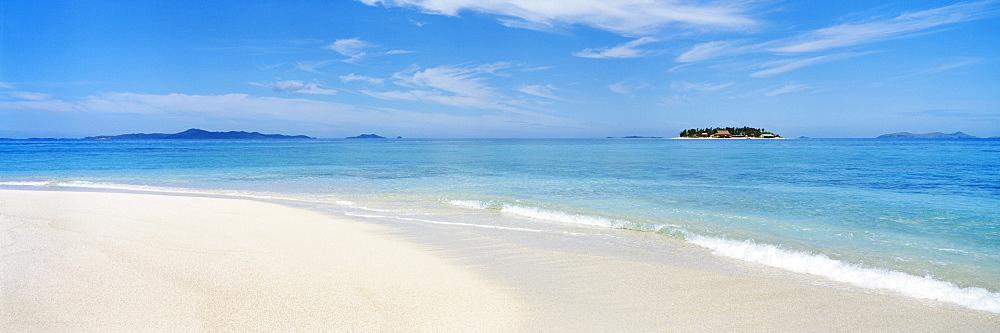 Fiji, Beachcomber Island, White sand beach and calm blue ocean water.