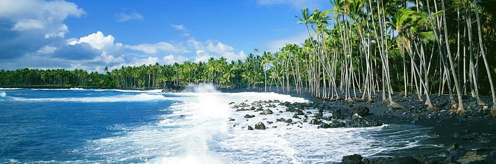 Hawaii, Big Island, Ocean surf crashing on Kalapana Black Sand Beach.