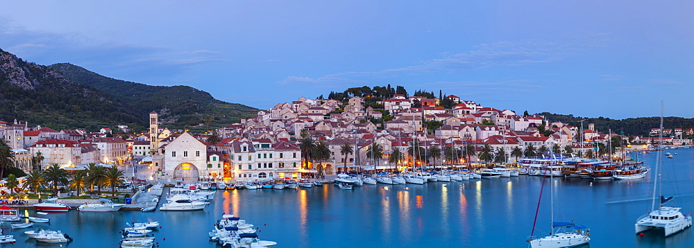 Elevated view over the picturesque harbour town of Hvar illuminated at dusk, Hvar, Dalmatia, Croatia, Europe