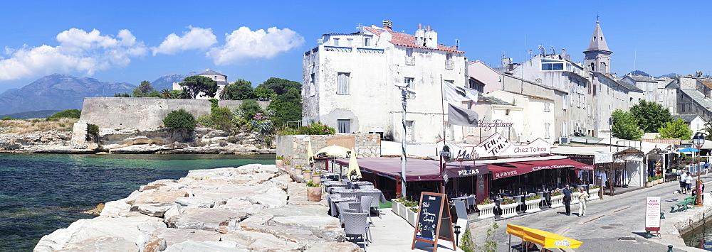 Promenade at the port of Saint Florent with the church of Santa Maria Assunta and the Citadel, Saint Florent, Corsica, France, Mediterranean, Europe