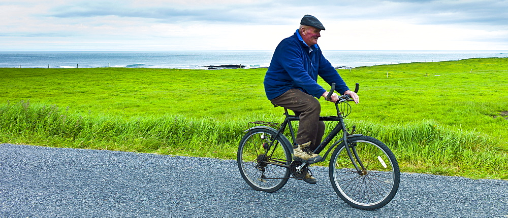 Local Irish man cycling traditional bicycle along country lane in County Clare, West of Ireland - 1161-6624