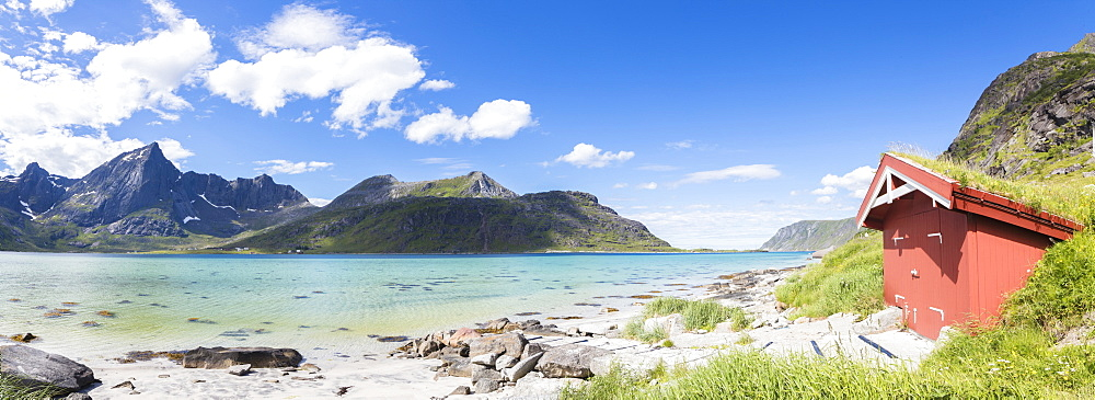 Panorama of the turquoise sea surrounded by peaks and typical house of fishermen, Strandveien, Lofoten Islands, Norway, Scandinavia, Europe