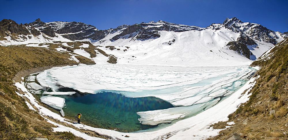 Photographer at Laj dal Teo where snow begins to melt due to spring thaw, Poschiavo Valley, Switzerland, Europe