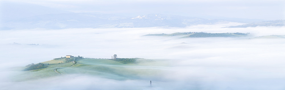 Panoramic view of the Val d'Orcia with fog dispersing to reveal a Tuscan farmhouse perched on a small hill
