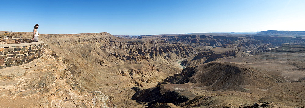 A woman looks into The Fish River Canyon in southern Namibia, Africa