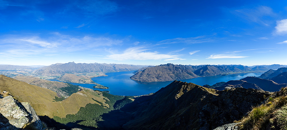 Steep sharp mountains, a deep blue lake, and mountain town in Queenstown, Otago, South Island, New Zealand, Pacific