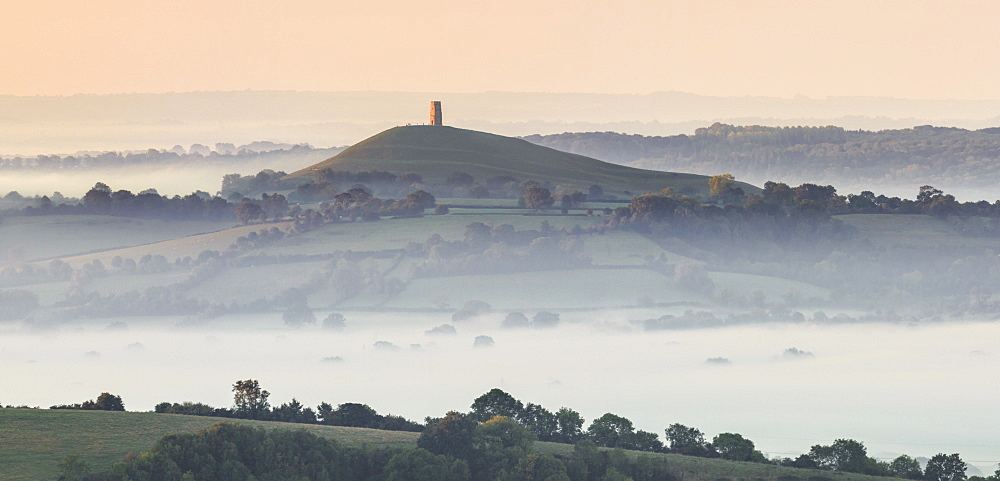Glastonbury Tor rising above a misty landscape on an autumn morning, Somerset, England, United Kingdom, Europe