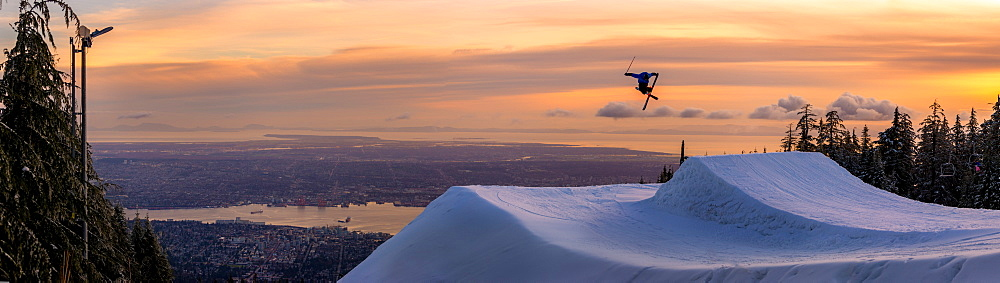 Freestyle skier doing a trick off a jump above city at sunset, Canada, North America - 1258-9