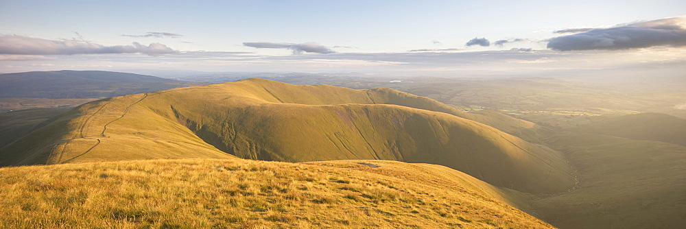 Arant Haw and the Howgill Fells lit by warm evening light from the summit of Calders, Sedbergh, Yorkshire Dales, Cumbria, England, United Kingdom, Europe