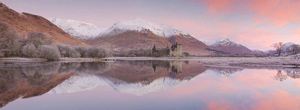 Stitched panoramic image of Kilchurn Castle and Loch Awe at sunrise with snow capped mountains in winter, Argyll and Bute, Scotland, United Kingdom, Europe