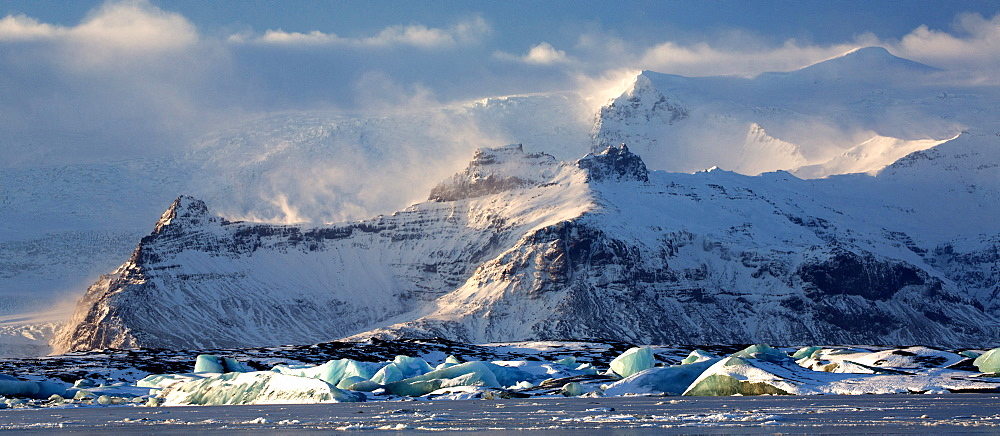 Winter view over frozen Jokulsarlon Glacier Lagoon showing blue icebergs covered in snow and distant mountains, South Iceland, Polar Regions