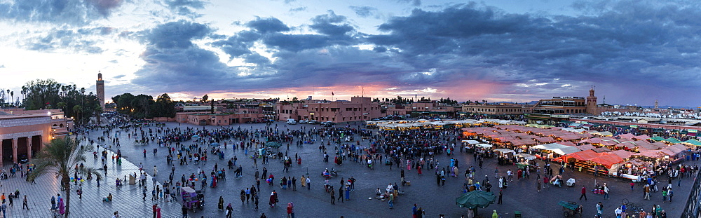 Panoramic view over the Djemaa el Fna at sunset showing Koutoubia Minaret, food stalls, shops and crowds, Marrakech, Morocco, North Africa, Africa - 321-5857