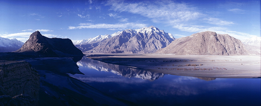 Panorama of mountains reflected in the water of the Indus River, Skardu, Baltistan, Pakistan, Asia