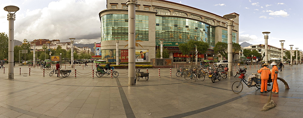 Panorama showing the Potala Palace in the distance and a department store on a modern high street, Lhasa, Tibet, China, Asia