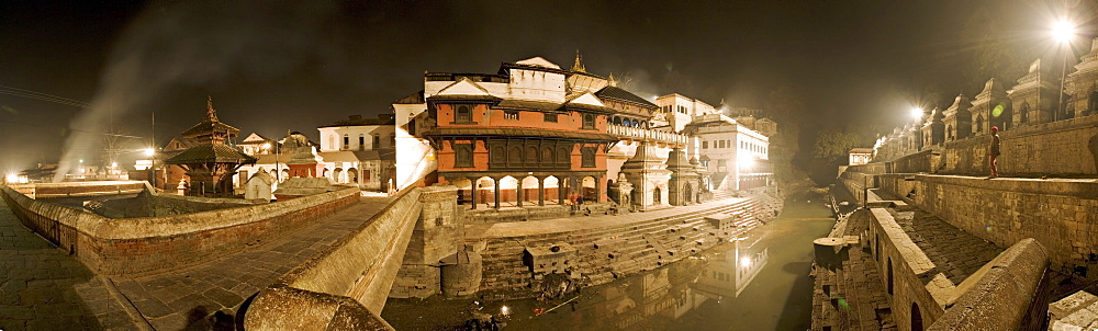 Smoke from funeral pyres on the ghats on the left drifts across the bridge over the river Bagmati at Nepal's holiest Hindu pilgrimage site, Pashupatinath, Kathmandu, Nepal, Asia