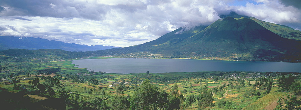 Imbabura Volcano, 4609 meters high above the waters of Laguna San Pablo with the fields around the town of Otavalo in the foreground, Highlands north of Quito, Ecuador