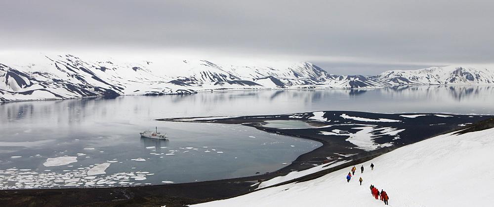 Tourists hiking down the mountainside towards Whalers Bay, Deception Island, South Shetland Islands, Antarctic Peninsula, Antarctica, Polar Regions