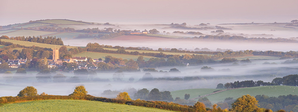 Rural Dartmoor village and church tower surrounded by mist covered countryside at dawn, South Tawton, Devon, England, United Kingdom, Europe