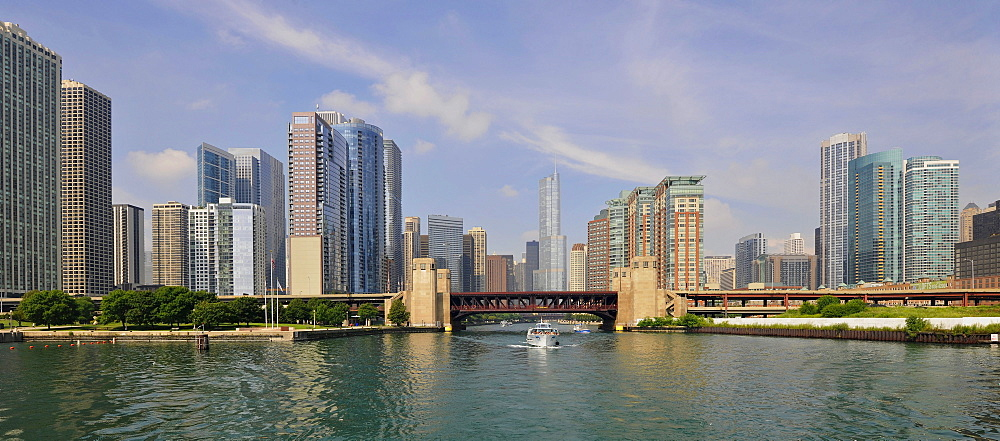 Excursion boat in front of the bridge on North Lakeshore Drive crossing the Chicago River, behind, the skyline with Trump International Tower, 3 Illinois Center, Swissotel and the Aqua Building, Chicago, Illinois, United States of America, USA