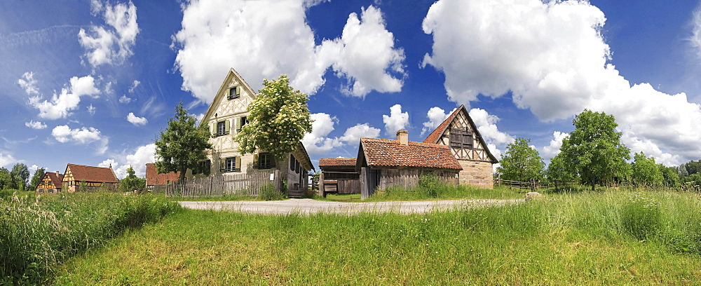 Panorama of an old farming village in the Regnitz region with clouds in the sky village green, Franconian Open-air Museum of Bad Windsheim, Bavaria, Germany, Europe