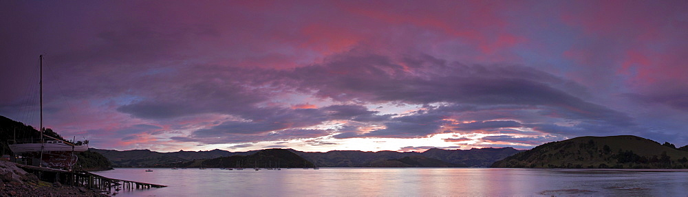 A colorful sunrise over Akaroa Harbor at the Banks Peninsula, New Zealand