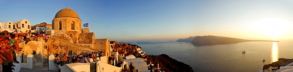 Tourists are waiting at the western part of the village for the sunset, Oia, Santorini, Greece