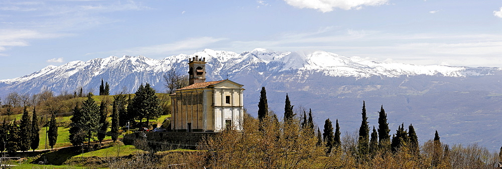 Church and the snow covered Monte Baldo massiv, Sasso, Garda lake, Italy