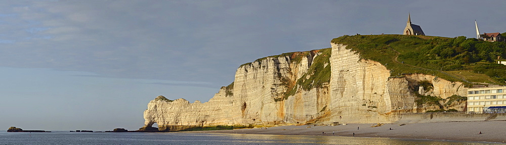 The chalk cliffs of Étretat with the natural arch Falaise d'Amont or Porte d'Amont and the chapel Notre-Dame-de-la-Garde illuminated by warm evening light, Côte d'Albâtre, Département Seine-Maritime, Haute-Normandie, France, Europe