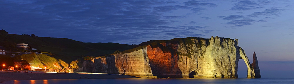 The chalk cliffs of Étretat with the natural arch Porte d'Aval and the needle Aiguille flood-lit at the blue hour after sunset, Côte d'Albâtre, Département Seine-Maritime, Haute-Normandie, France, Europe