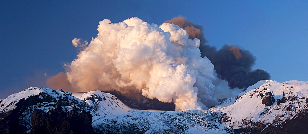 Panoramic shot of two clouds from the volcanic eruption in Eyjafjallajoekull Volcano, the black cloud at the rear is coming from the crater, the white cloud at the front is the result of a lava flow in a glacier, Eyjafjallajoekull, Iceland, Europe