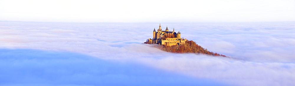 Burg Hohenzollern castle in morning light, mist, with autumn forest, Schwaebische Alb, Swabian Alb, Baden-Wuerttemberg, Germany, Europe