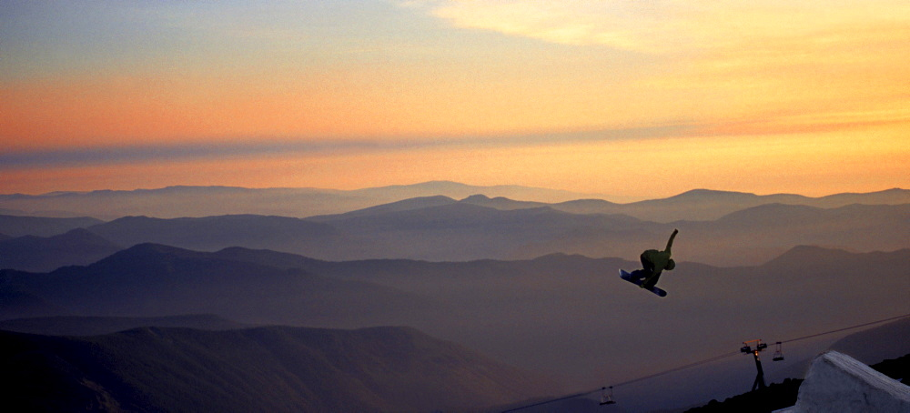 A snowboarder pulls a grab during sunset at Mt. Hood, Timberline.