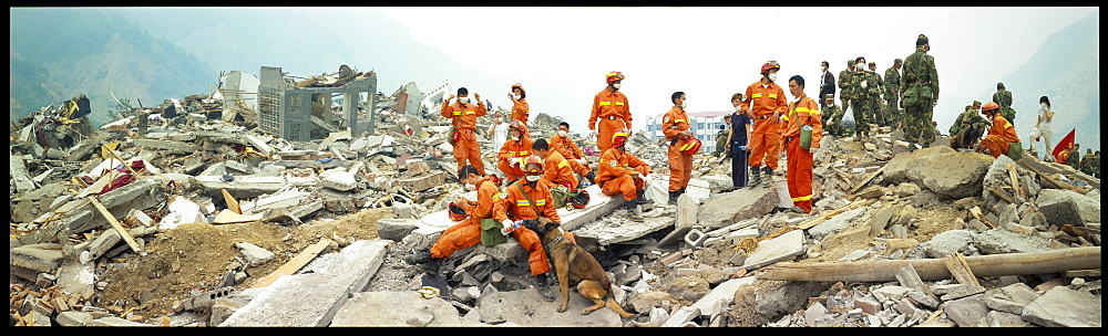 A rescue worker waters his dog  May 17 in Beichuan, China. The death toll in China's worst earthquake in 30 years could top 80, 000 according to the government. - 857-69403