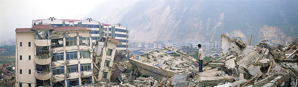 A survivor stands amid ruins in May 17 in Beichuan, China. The death toll in China's worst earthquake in 30 years could top 80, 000 according to the government.