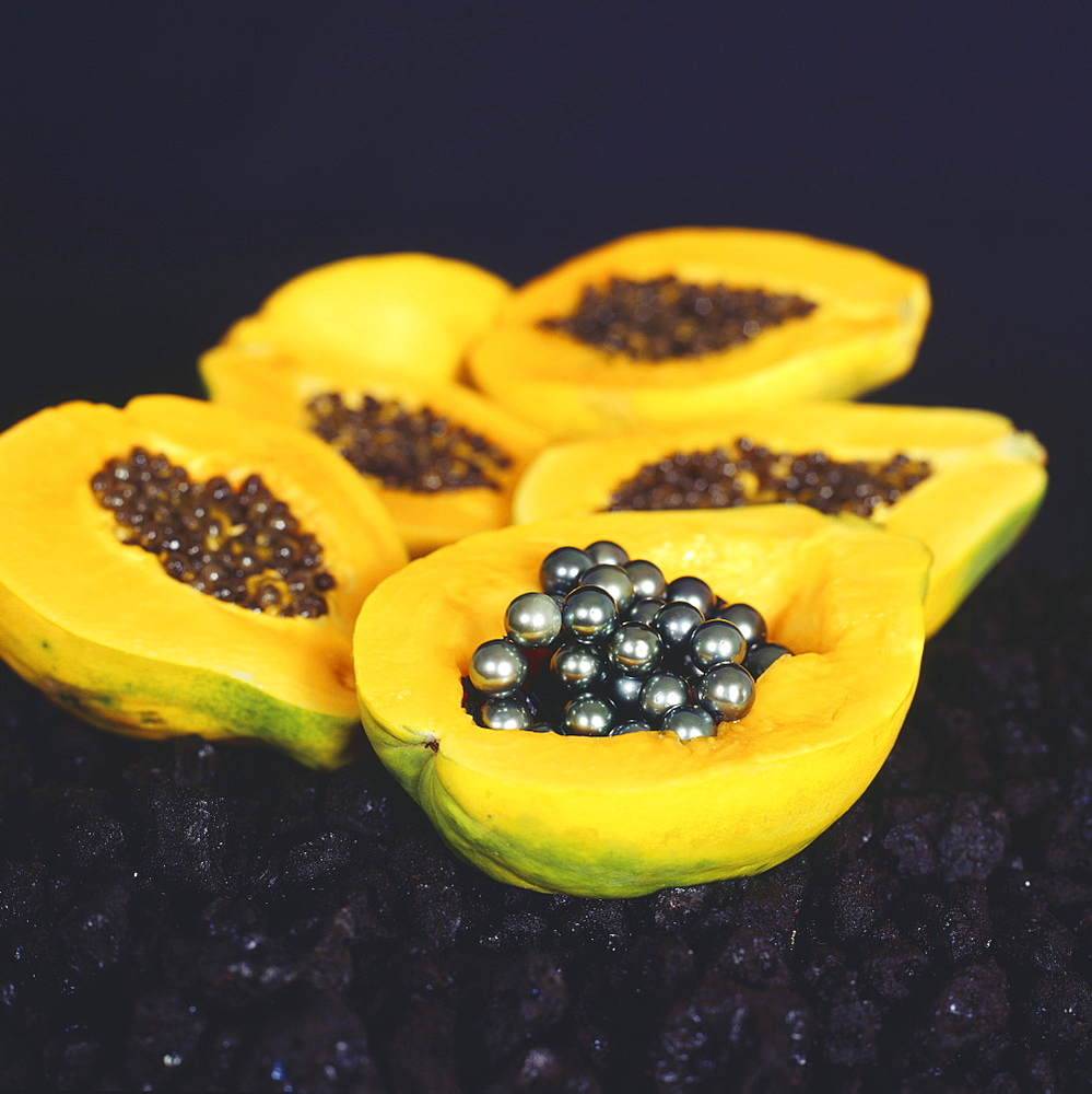 Cluster of papaya halves, one filled with black pearls.