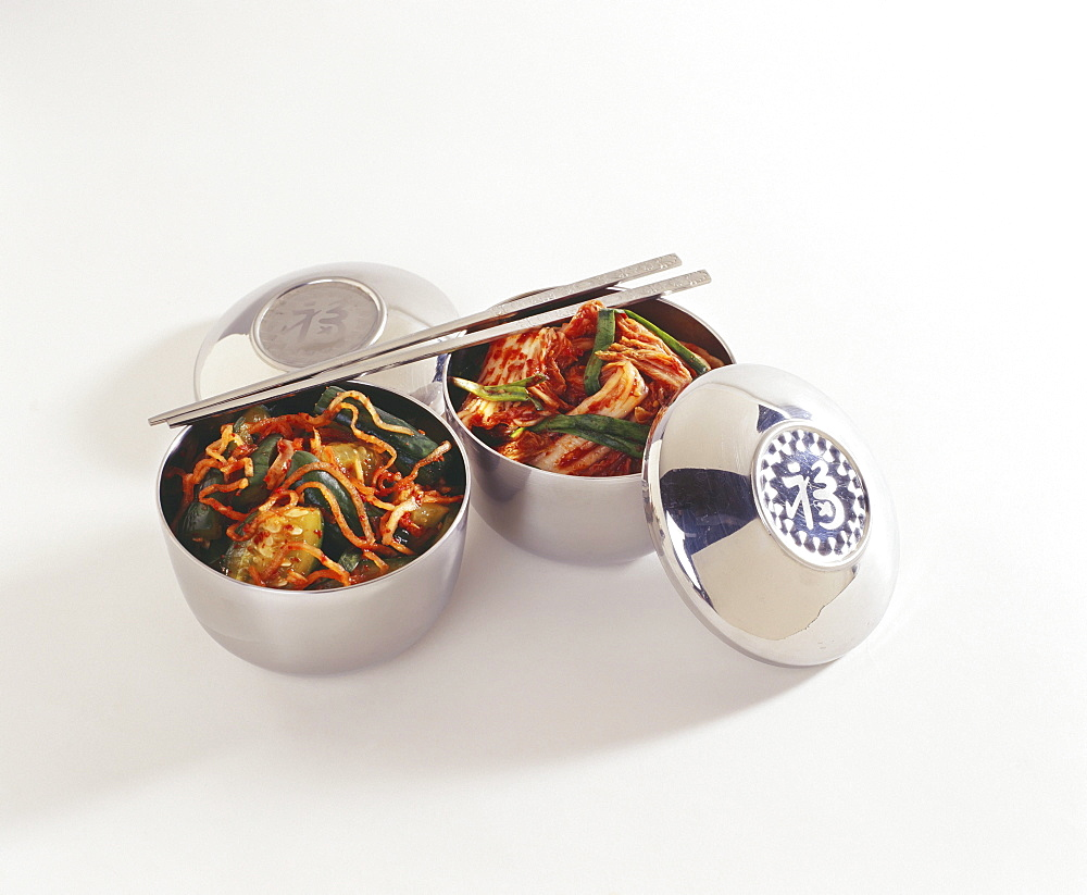 Studio shot of two bowls of kim chee with chopsticks.
