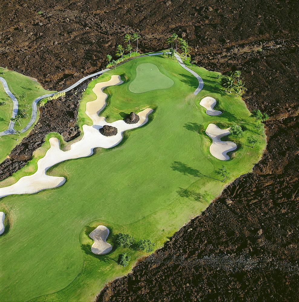Hawaii, Big Island, Aerial view of Waikoloa Resort hole #5 surrounded by lava field