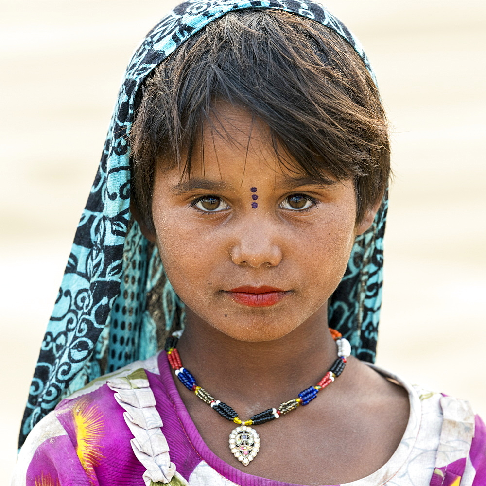 Portrait of a young Indian girl with markings on her face, Damodara, Rajasthan, India