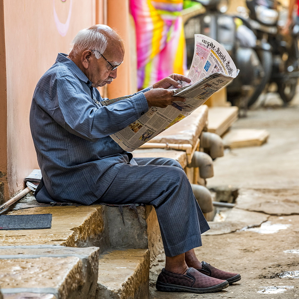 A senior man sits on the side of a street reading the newspaper, Jaisalmer, Rajasthan, India