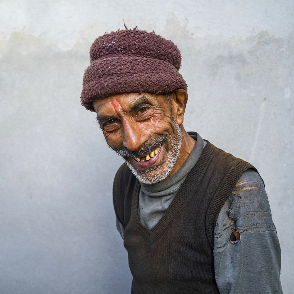Portrait of an Indian man with a toothy grin and wearing a hat, Radhu Khandu Village, Sikkim, India