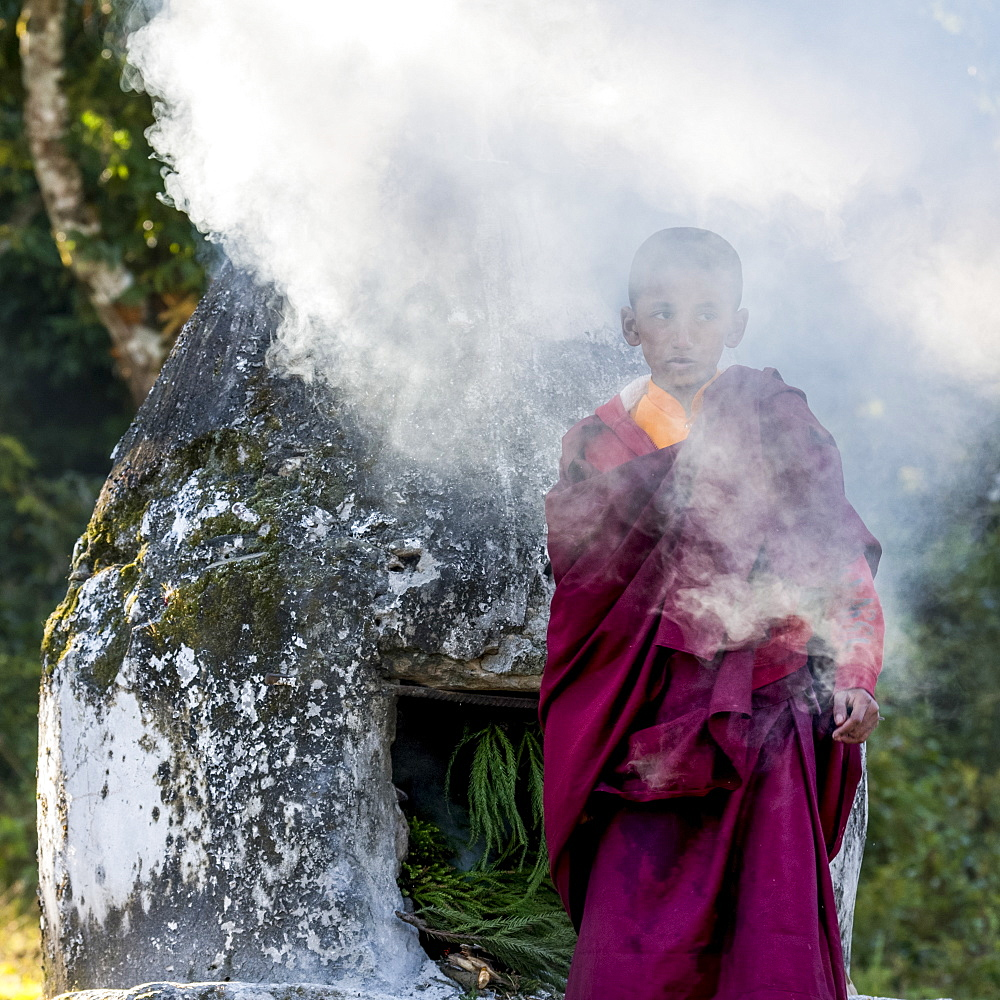 A young Buddhist monk stands outside in a shroud of smoke at Rinchenpong Monastery, Sikkim, India